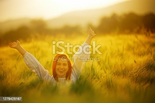 Redhead looking at camera with arms outstretched feeling happy and free in the wheat field