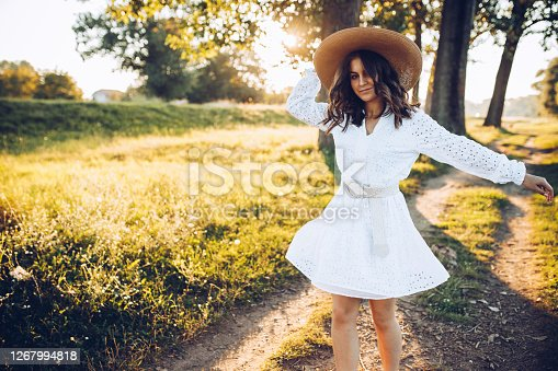 Young woman dancing in a summer field in Europe at sunset. She's wearing white clothes and a straw hat.