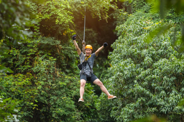 Freedom Man Tourist Wearing Casual Clothing On Zip Line Or Canopy Experience In Laos Rainforest, Asia stock photo