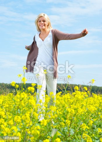 Carefree woman jumping in a meadow on a sunny day.