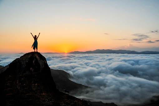 Woman enjoys on top of a cliff above the sea of clouds at sunset.