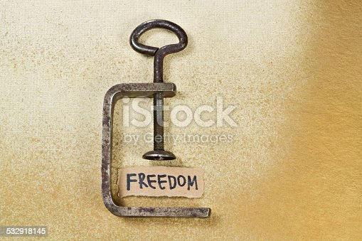 Word Freedom under pressure of clamp on yellow background