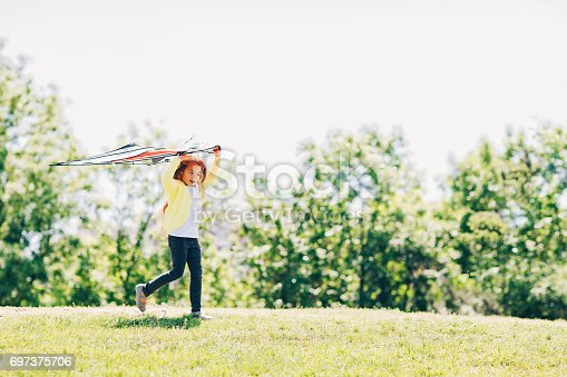 Small girl running with a kite outdoors on the field