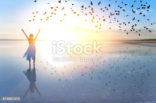 Woman on lake at sunset representing freedom