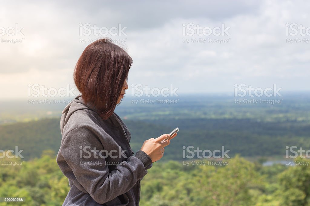 Freedom traveler woman standing playing mobile and beautiful nature. royalty-free stock photo