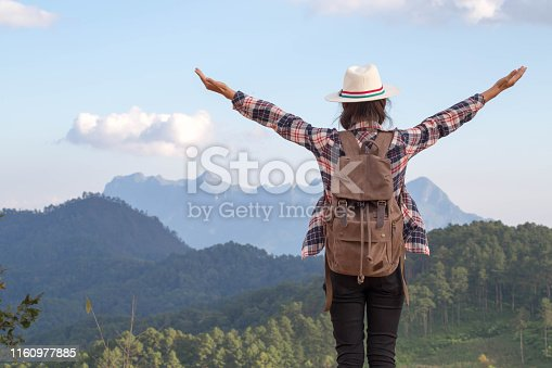 Freedom traveler woman standing with raised arms and enjoying a beautiful nature.