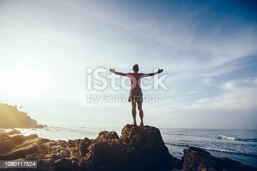 Freedom woman outstretched arms on sunrise seaside rock cliff edge