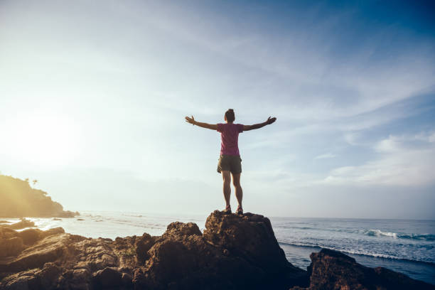 Freedom woman outstretched arms on sunrise seaside rock cliff edge stock photo