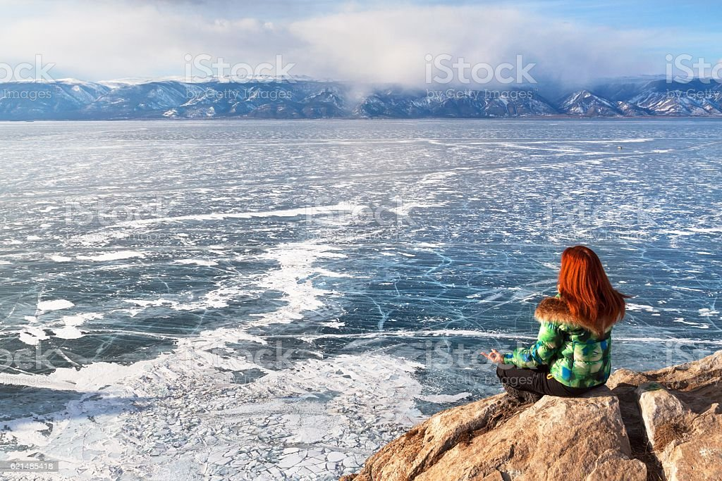 Freedom woman sitting in meditation frozen lake Baikal. Winter tourism photo libre de droits