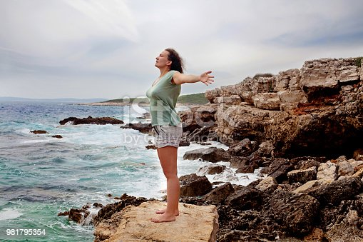 istock Freedom, woman with outstretched arms by the sea 981795354