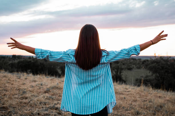 Freedom Young Woman Outdoors Enyoing the Sunset stock photo