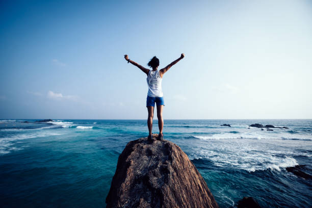 Freedom young woman outstretched arms on seaside rock cliff edge stock photo