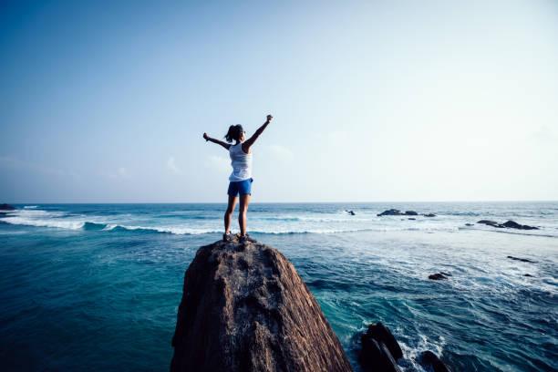 Junge Frau Freiheit ausgestreckten Arme auf Fels-Klippe am Meer – Foto
