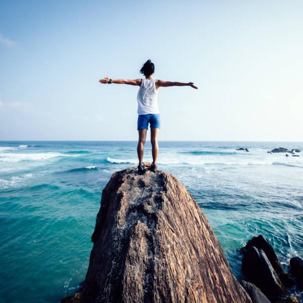 自由年輕女子伸出手臂在海邊岩石懸崖邊緣 - 休閒活動 主題 個照片及圖片檔