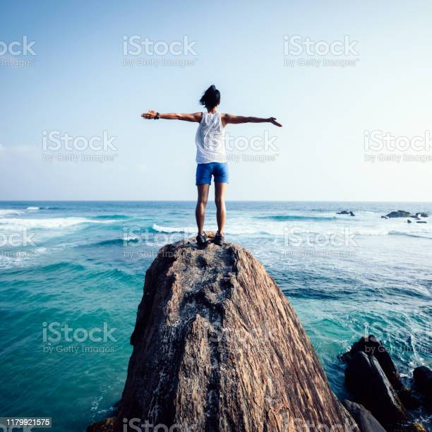 Photo of Freedom young woman outstretched arms on seaside rock cliff edge
