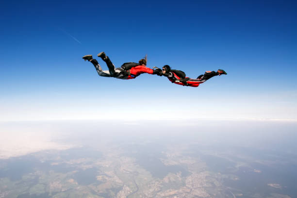 Freefall Two skydivers enjoy in free fall parachuting stock pictures, royalty-free photos & images
