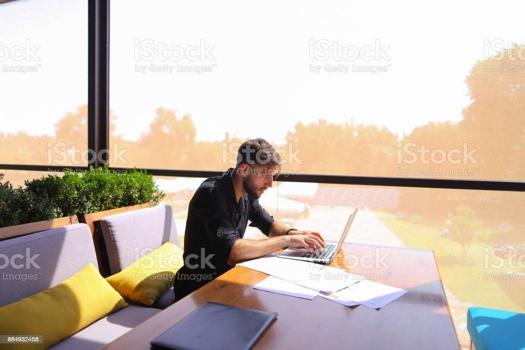 Freelance copywriter rewrite text on laptop at cafe table stock photo