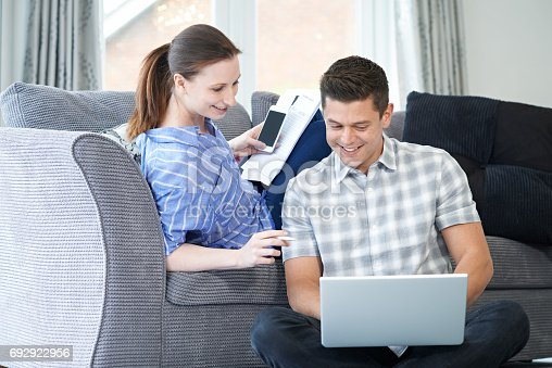 Freelance Couple Working From Home Looking At Laptop Together