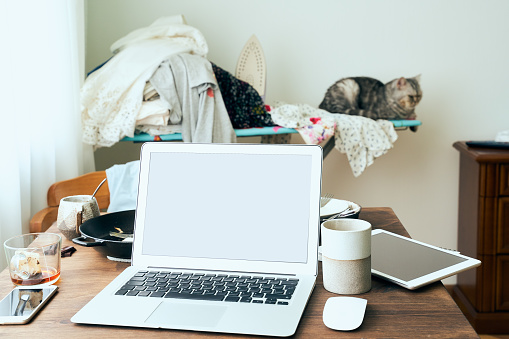 Freelance Desk with laptop in mess at home apartment. Quarantine, self-isolation, sociophobia