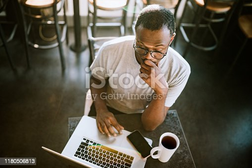A young African American man works in his local coffee shop on his laptop, making progress on a project for a client.