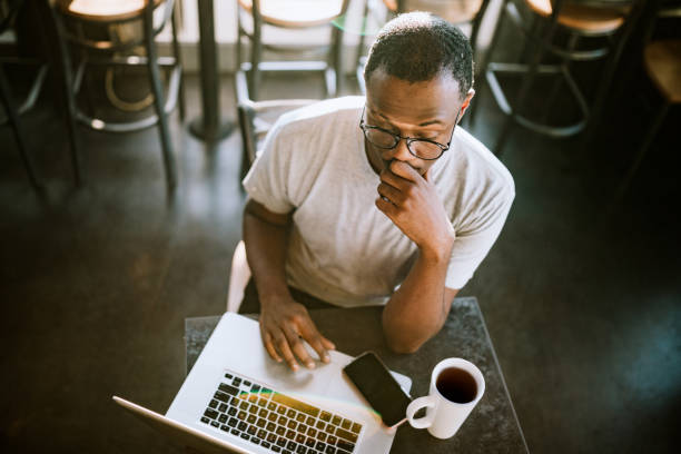 Freelance Entrepreneur Working Remotely A young African American man works in his local coffee shop on his laptop, making progress on a project for a client. pierce county washington state stock pictures, royalty-free photos & images