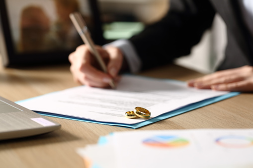 Freelance hands signs divorce papers at night