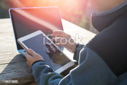 1016971522 istock photo Freelance man using multichannel online network 5G technology internet tablet and laptop working in nature park during relax day time.Sunlight morning, work from anywhere life style concept. 1166374835