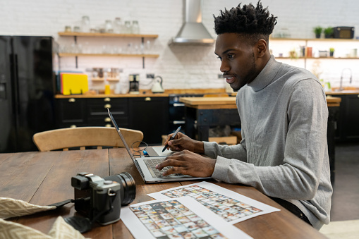 African American freelance photographer editing photos at home using a laptop computer and a pen tablet. **IMAGES BELONG TO US**