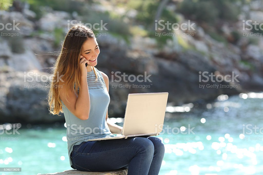 Freelance woman working in vacation on the phone stock photo