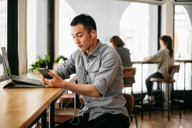 Freelance worker wearing earphones and text messaging on smartphone stock photo