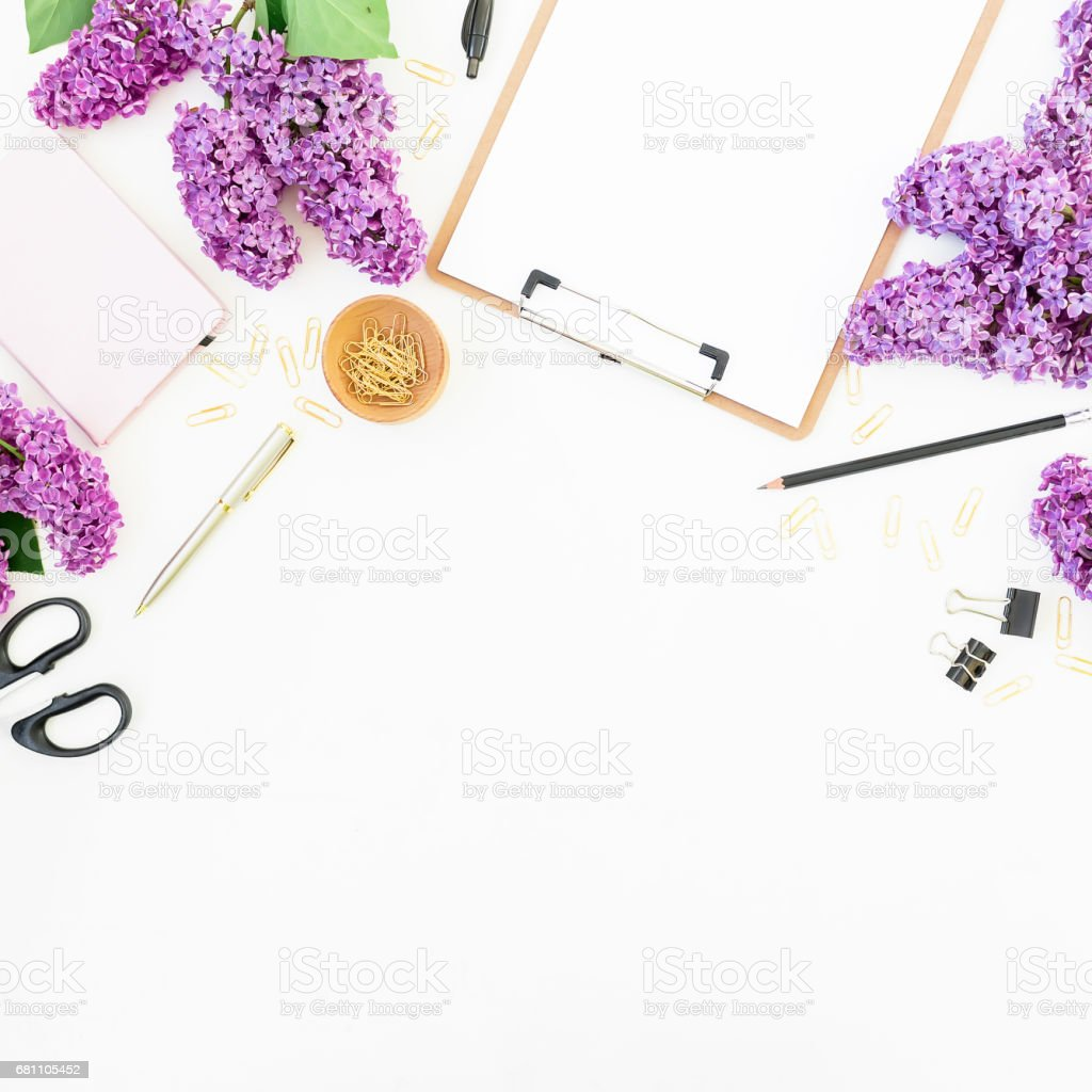 Freelance workspace with clipboard, mobile phone, notebook, scissors, lilac and accessories on white background. Flat lay, top view. Beauty blog concept. royalty-free stock photo