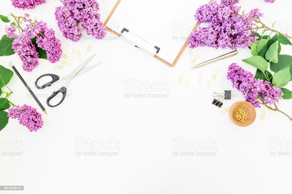 Freelance workspace with clipboard, pen, scissors, lilac and...
