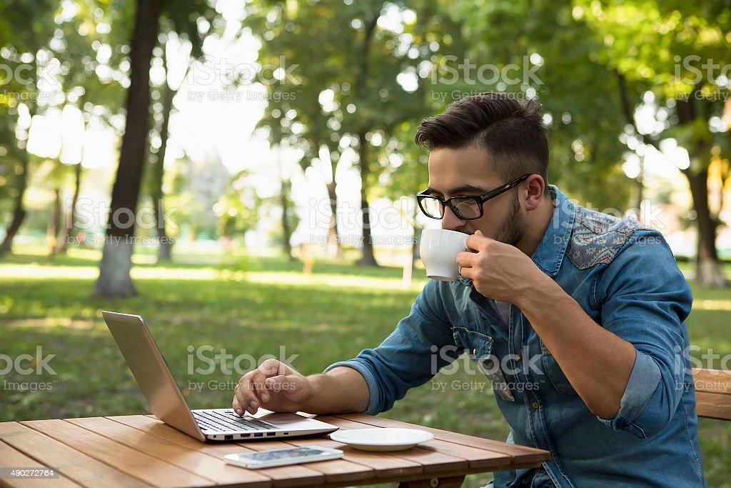 Freelancer hipster man drinking coffee stock photo