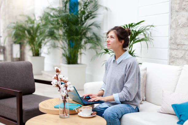 Freelancer is working in comfortable cafe. Happy girl with laptop in coworking modern office. Attractive businesswoman is dreaming, thinking, enjoying coffee and quiet space. Wellbeing in workplace. stock photo