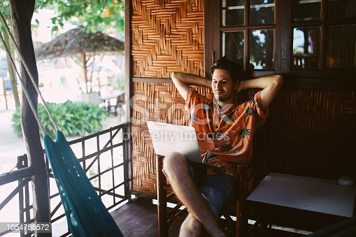 Young freelancer man, doing his work while relaxing near the beach on the island of Ko Phangan.