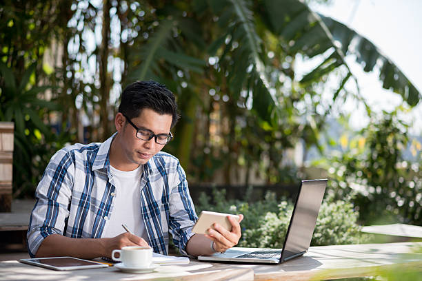 Freelancer Portrait of Vietnamese male freelancer working in cafe copywriter stock pictures, royalty-free photos & images