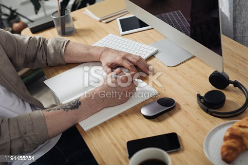 Hands of a Caucasian freelancer man writing on a paper in the modern office space.