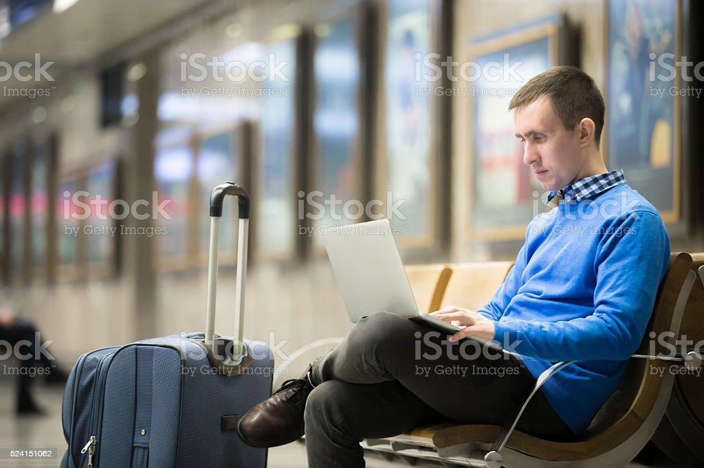 Freelancer traveler waiting at transport station stock photo