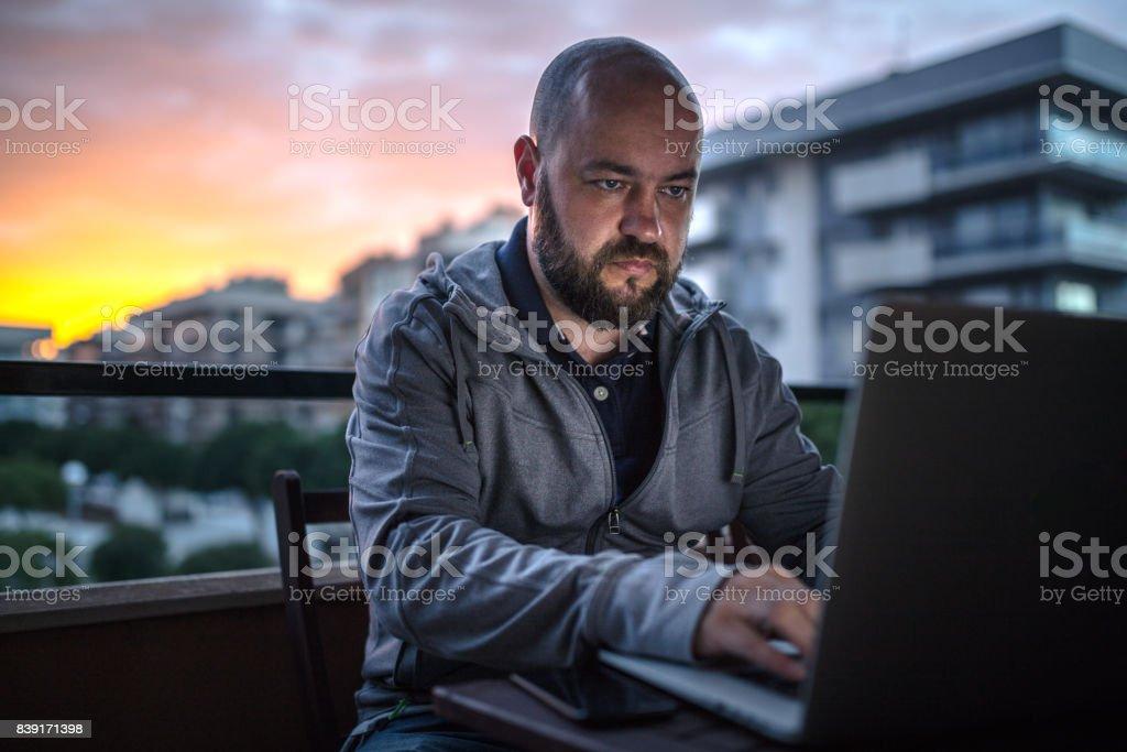 Freier Mitarbeiter nutzt Laptop auf dem Balkon bei Sonnenuntergang – Foto
