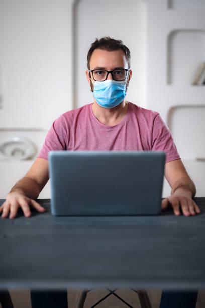 Freiberufler mit medizinischer Schutzmaske arbeiten von zu Hause aus in den Tagen der Pandemie und soziale Abstand. – Foto