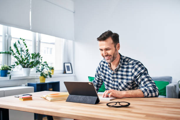 Freelancer working from home sitting at desk with digital tablet stock photo