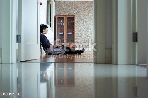A young woman sitting on the floor of her flat, working on her laptop.