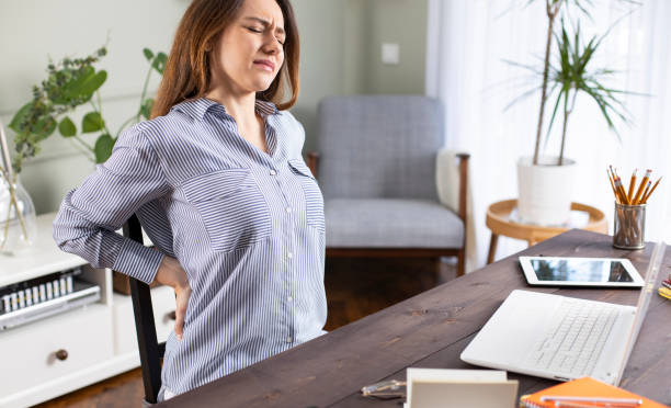 Freelancer young woman suffering with back pain Freelancer young woman suffering with back pain while working in her office at home back pain stock pictures, royalty-free photos & images