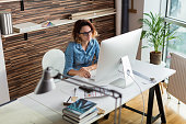 Female designer working online on a computer.