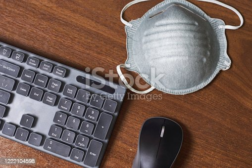PC keyboard and protective medical face mask. Freelancing, working from home and stay at home concepts