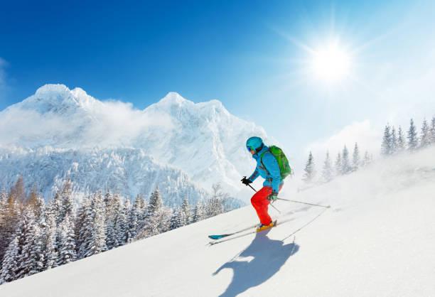 Free-ride skier in fresh powder snow running downhill stock photo