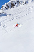 one male skier facing forward in the middle of the turn, powder snow, white background