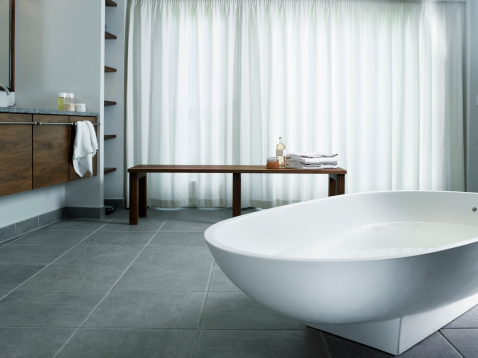 Bathtub on tiled floor with curtains and bench