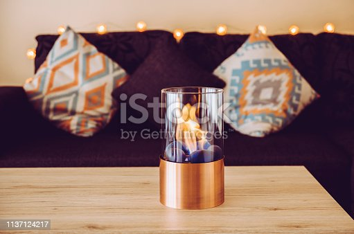 istock Freestanding portable glass and copper metal fireplace burning bio ethanol gas on living room wooden table. Autumn comfortable colorful cozy home set. 1137124217