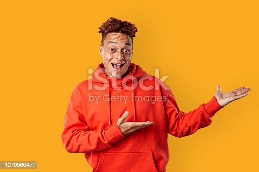 Young freckled mulatto man wearing red hoodie standing isolated on yellow background showing copy space for text or product looking camera smiling excited